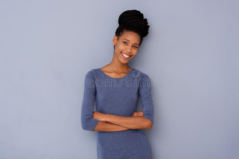 Cute young girl standing with arms crossed and smiling against gray background stock images