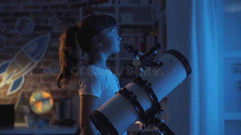 Cute girl stargazing at night stock images