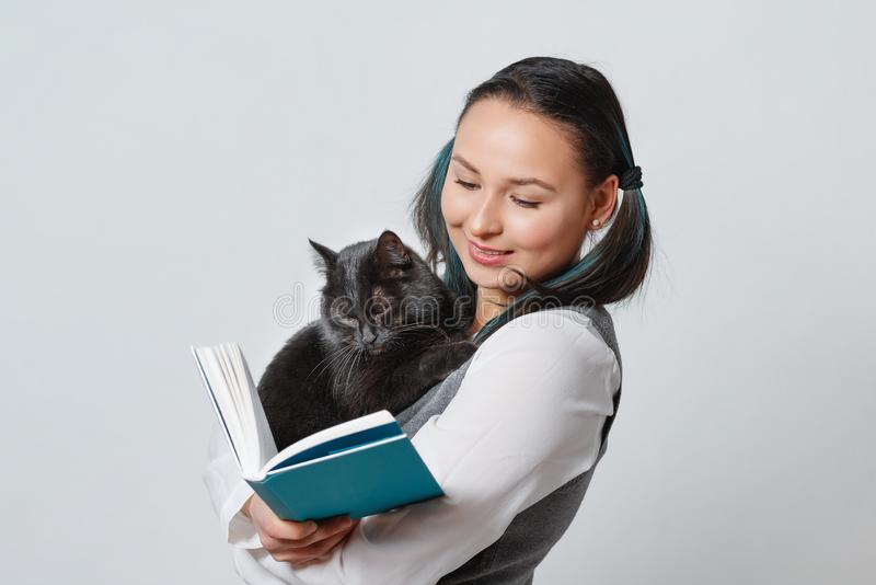 Cute young girl student with a funny cat in her arms reading a book. On light background stock photos