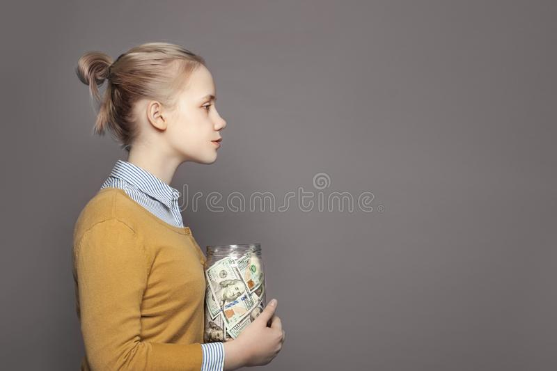 Cute young girl teenager saving money in glass jar. Education fees and saving money concept royalty free stock image