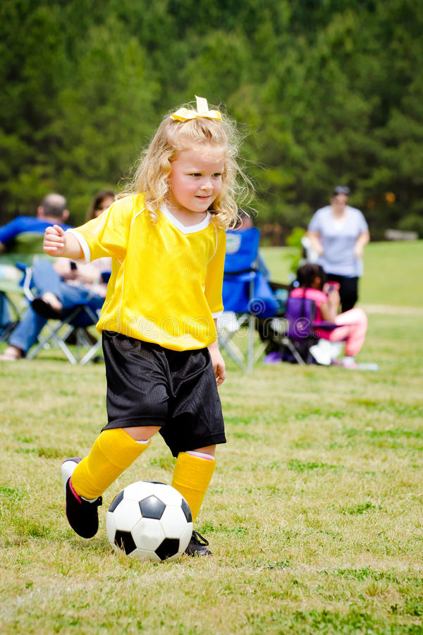 Cute young girl in uniform playing soccer royalty free stock photos