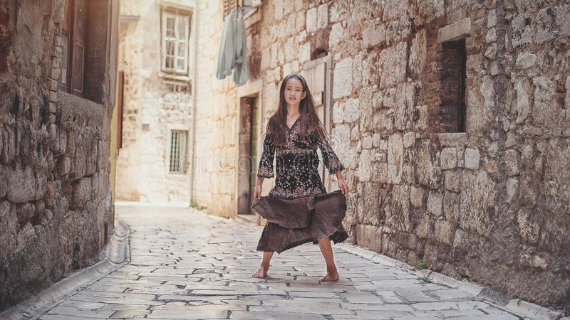 Cute young girl walking in the old town. Nice female child in medieval city. stock photography