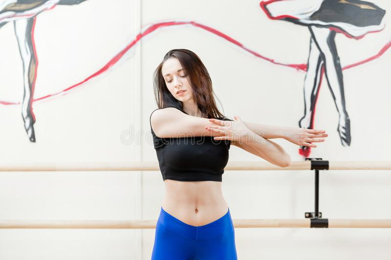 Cute young girl wearing black top and blue pants doing physical exercises warming up. Physical activity concept. Cute young girl wearing black top and pants royalty free stock photography