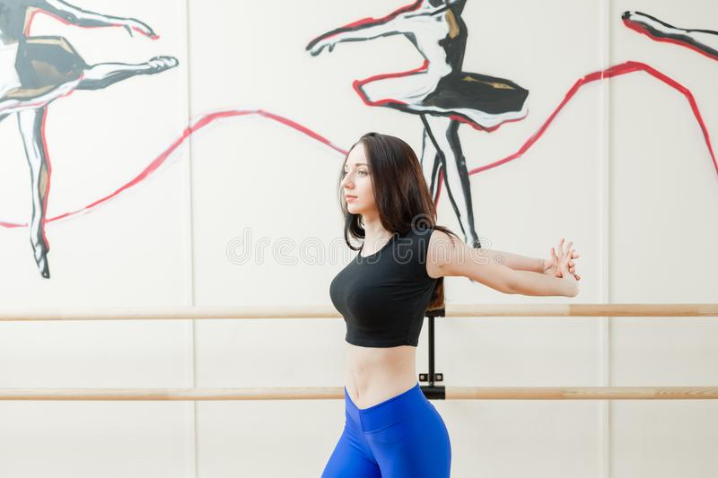 Cute young girl wearing black top and blue pants doing physical exercises warming up. Physical activity concept. Cute young girl wearing black top and pants stock photos