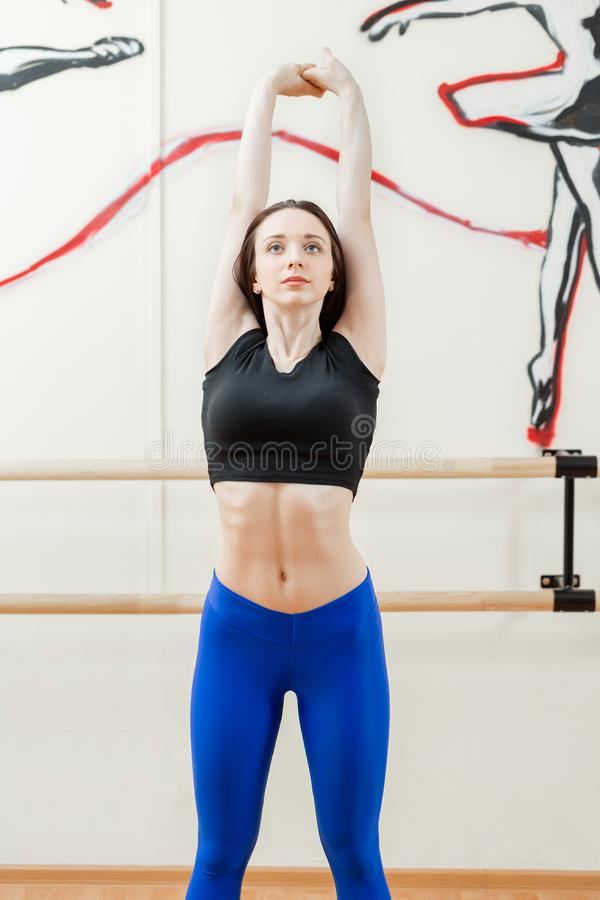 Cute young girl wearing black top and blue pants doing physical exercises warming up. Physical activity concept. Cute young girl wearing black top and pants stock image