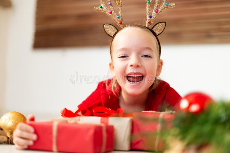Cute young girl wearing costume reindeer antlers lying on the floor, surrounded by many christmas presents, screaming with joy. stock image