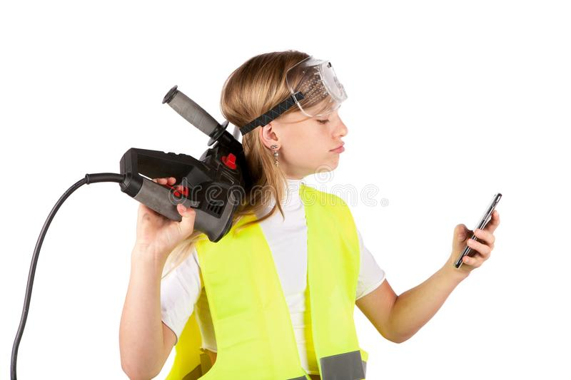 Cute young girl wearing safety vest and safety goggles, holding a rotary hammer and using a smartphone. royalty free stock photo