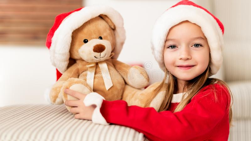 Cute young girl wearing santa hat hugging her christmas present, soft toy teddy bear. Happy kid with xmas present, smiling. stock photo