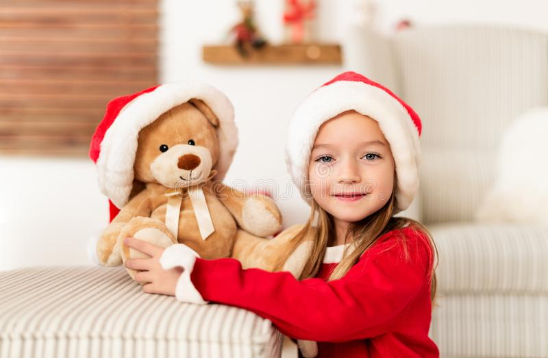 Cute young girl wearing santa hat holding her christmas present, soft toy teddy bear. Happy kid with xmas present, smiling. stock photos