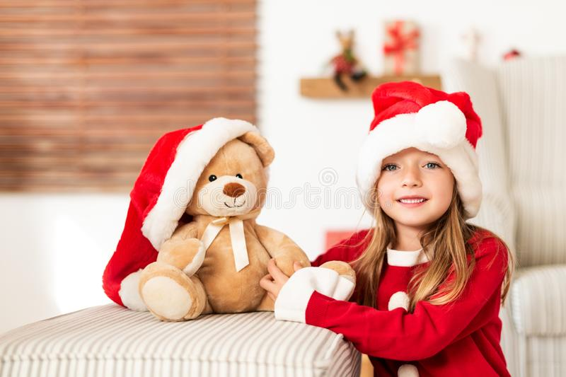 Cute young girl wearing santa hat holding her christmas present, soft toy teddy bear. Happy kid with xmas present. royalty free stock images