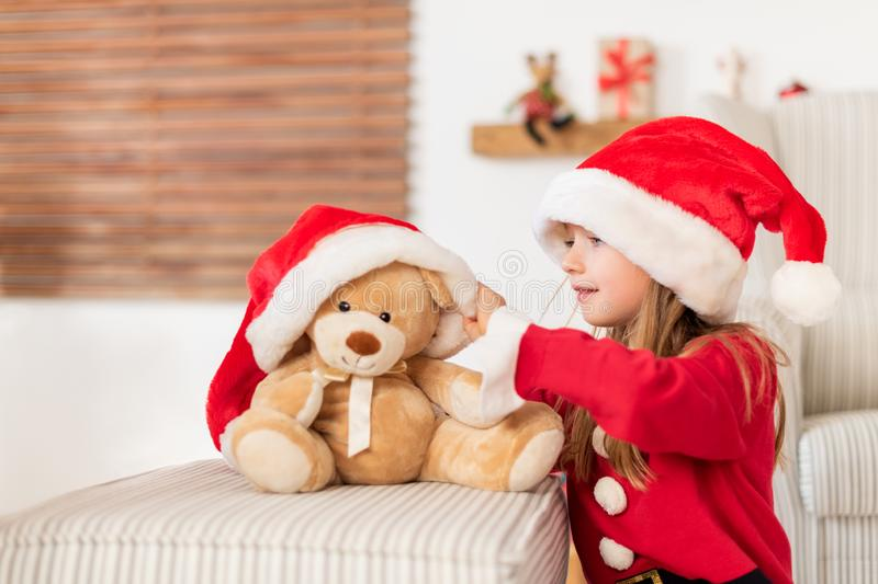 Cute young girl wearing santa hat playing with her christmas present, soft toy teddy bear. Playful kid at christmas time. royalty free stock photography