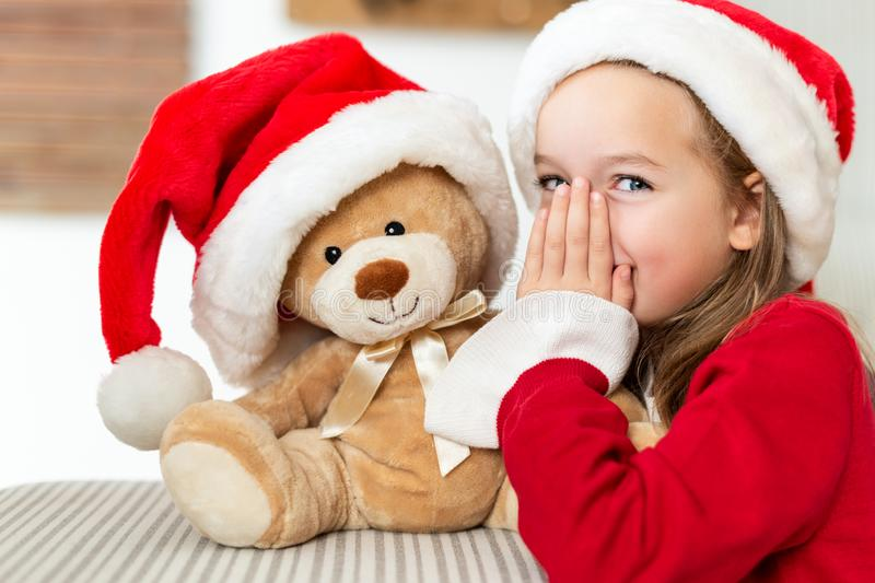 Cute young girl wearing santa hat whispering a secret to her teddy bear christmas present toy. Cheeky kid with teddy bear. royalty free stock image