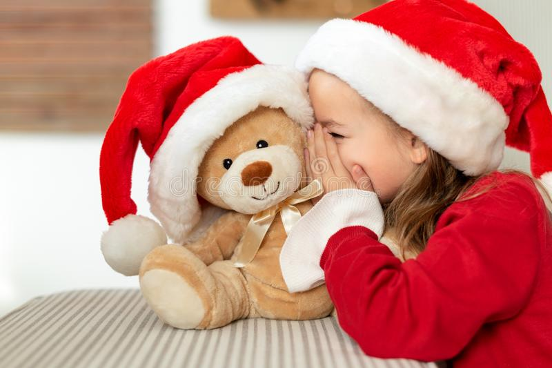 Cute young girl wearing santa hat whispering a secret to her teddy bear christmas present toy. Kid sharing secrets with teddy bear royalty free stock photography