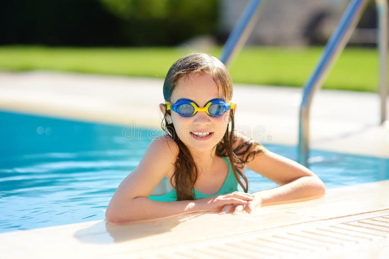 Cute young girl wearing swimming goggles having fun in outdoor pool. Child learning to swim. Kid having fun with water toys. Family fun in a pool royalty free stock images