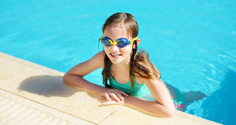 Cute young girl wearing swimming goggles having fun in outdoor pool. Child learning to swim. Kid having fun with water toys. Family fun in a pool royalty free stock photography