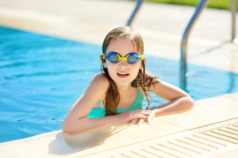 Cute young girl wearing swimming goggles having fun in outdoor pool. Child learning to swim. Kid having fun with water toys. Family fun in a pool royalty free stock image