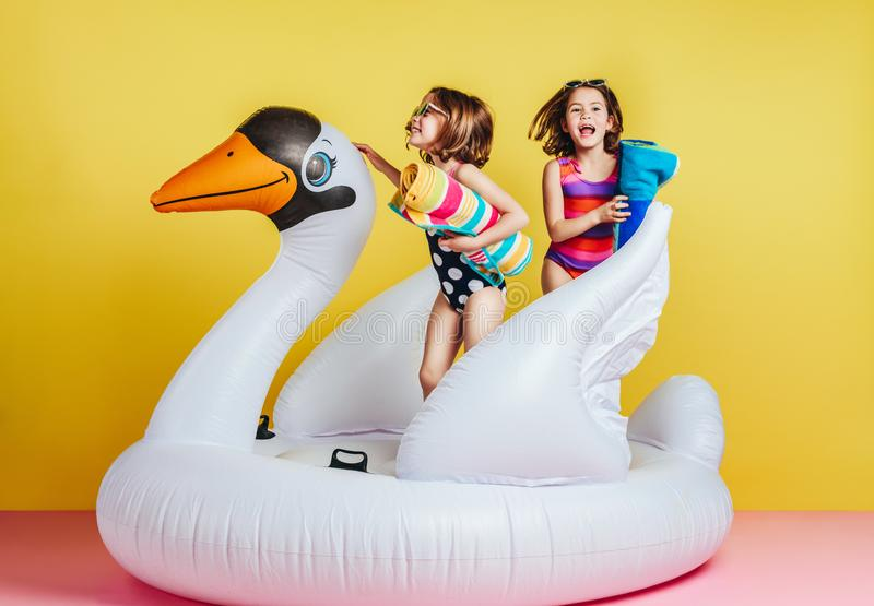 Cute young girls playing on inflatable mattress royalty free stock photography