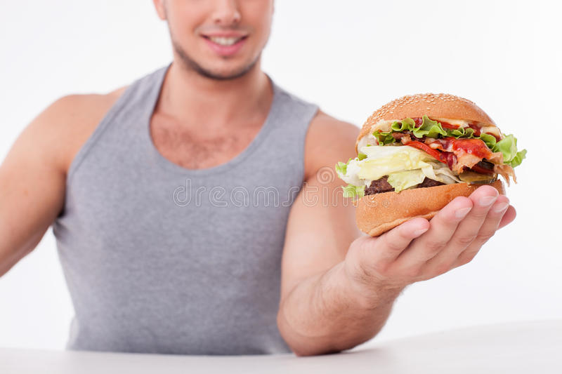 Cute young guy is proposing unhealthy food. Close up of man holding a hamburger and showing it to camera. He is sitting at the table and smiling. Focus on a royalty free stock images