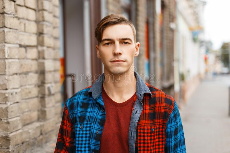 Cute young handsome man with a stylish hairstyle in a trendy T-shirt in a fashionable plaid shirt walks in the city. Near a vintage brick building on a summer royalty free stock photography