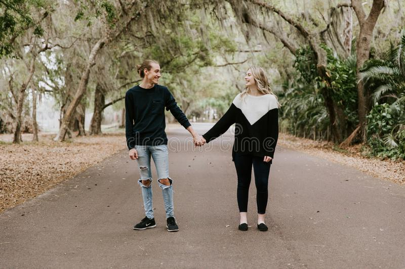 Cute Young Happy Loving Couple Walking Down an Old Abandoned Road with Mossy Oak Trees Overhanging. Outside talking and holding hands royalty free stock photography