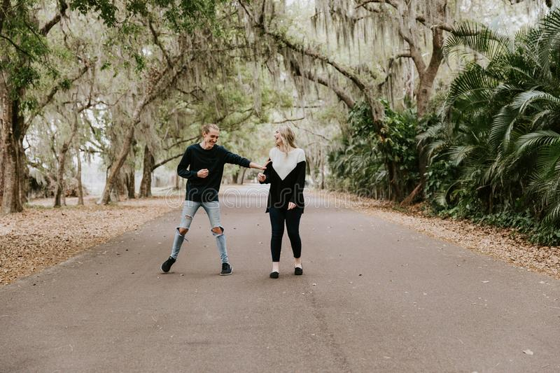 Cute Young Happy Loving Couple Walking Down an Old Abandoned Road with Mossy Oak Trees Overhanging. Outside talking and holding hands royalty free stock images