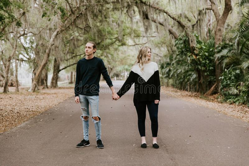 Cute Young Happy Loving Couple Walking Down an Old Abandoned Road with Mossy Oak Trees Overhanging. Outside talking and holding hands stock photography