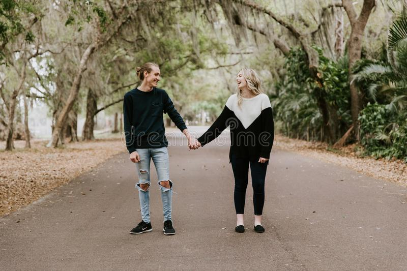 Cute Young Happy Loving Couple Walking Down an Old Abandoned Road with Mossy Oak Trees Overhanging. Outside talking and holding hands stock photo