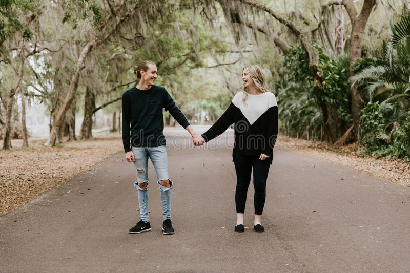 Cute Young Happy Loving Couple Walking Down an Old Abandoned Road with Mossy Oak Trees Overhanging. Outside talking and holding hands royalty free stock photos