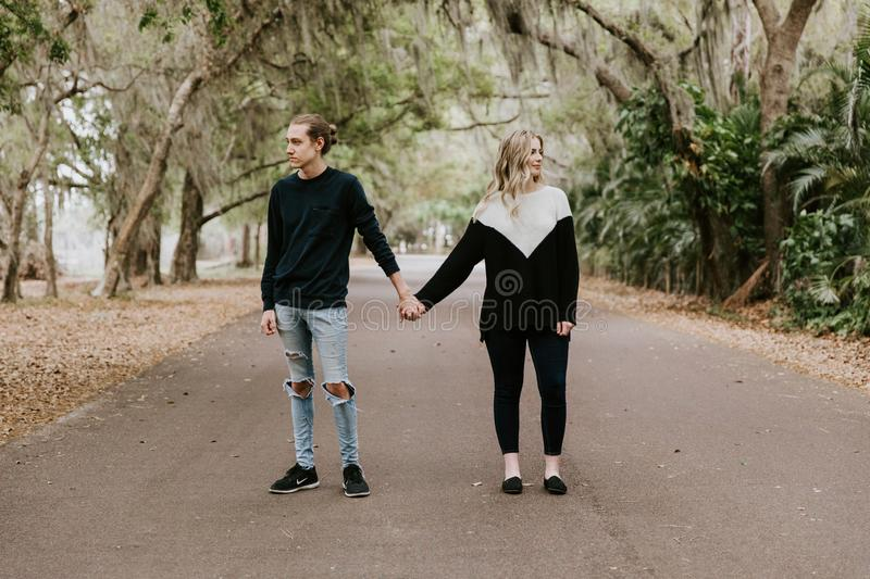 Cute Young Happy Loving Couple Walking Down an Old Abandoned Road with Mossy Oak Trees Overhanging. Outside talking and holding hands stock images