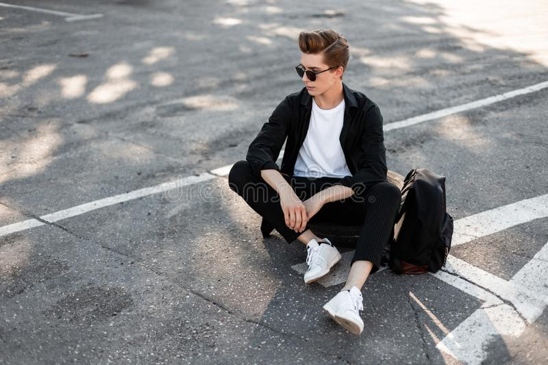 Cute young hipster man in black elegant stylish clothes in trendy sunglasses in fashionable white sneakers is sitting. On the asphalt in the city. Attractive stock photos