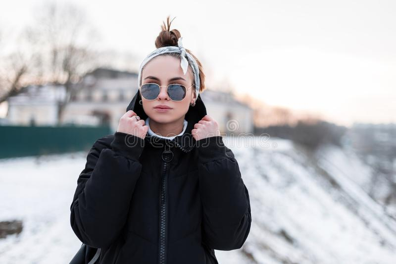 Cute young hipster woman in stylish black sunglasses in black trendy winter jacket with a leather backpack with a bandana royalty free stock photos
