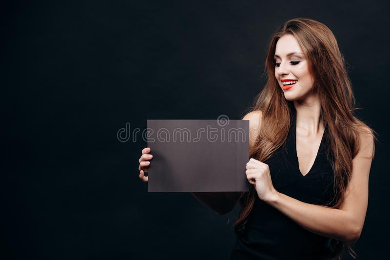 Cute Young Lady Demonstrating Blank Dark Announcement royalty free stock photos