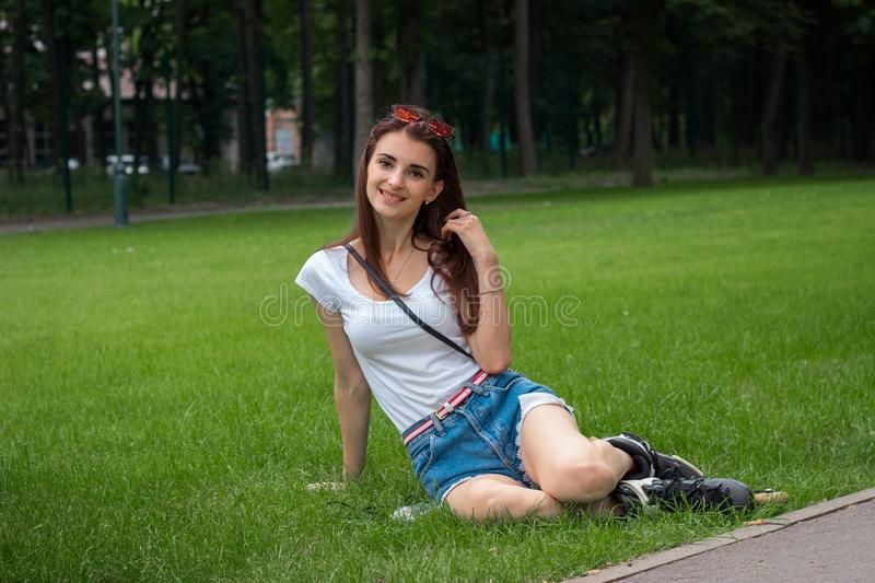 Cute young lady sitting in a park on green grass looks forward stock photo