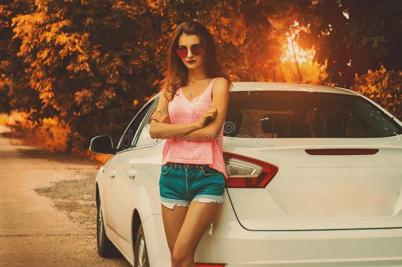 Cute young lady stands at the sunset stock image