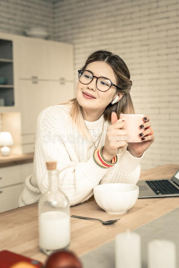 Cute young lady warming hands up with cup of tea royalty free stock image