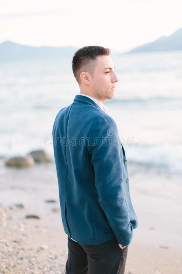A cute young man in a blue jacket walks along the lake Garda and looks at the water and the waves of the lake. stock photos