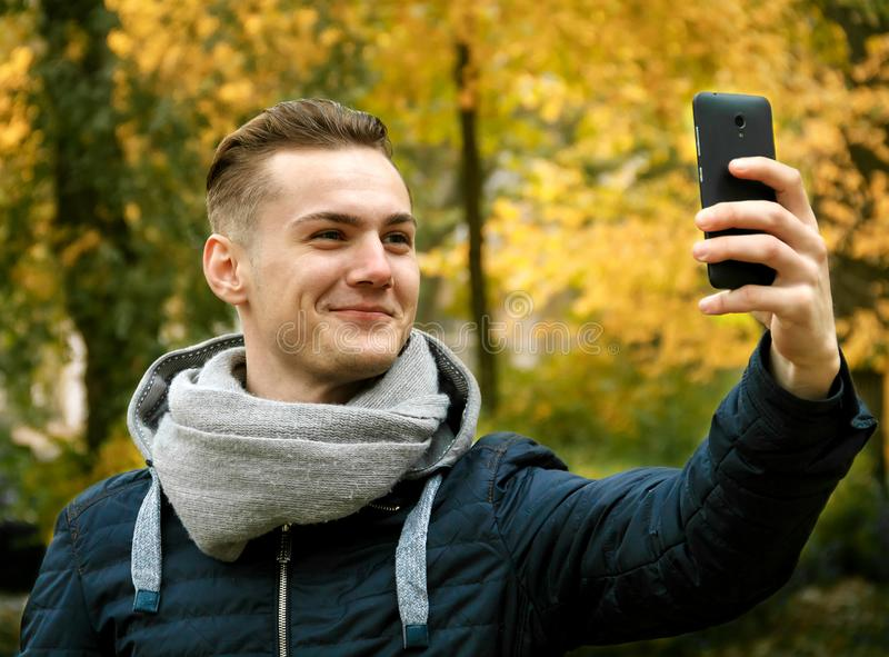 Cute young man with smartphone stock photo