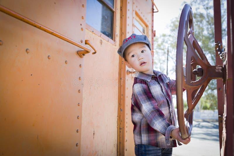 Cute Young Mixed Race Boy Having Fun on Railroad Car stock photo