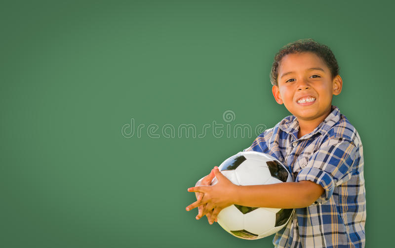 Cute Young Mixed Race Boy Holding Soccer Ball In Front of Blank. Cute Smiling Young Mixed Race Boy Holding Soccer Ball In Front of Blank Chalk Board stock images