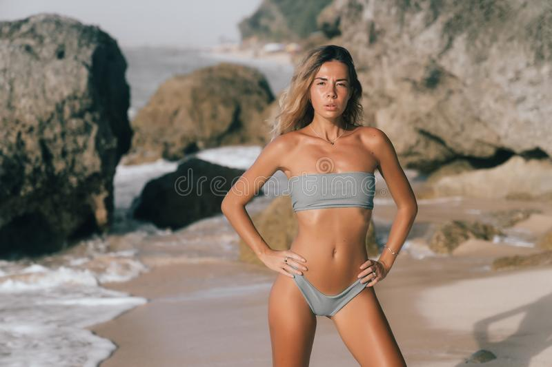 Cute young model with body in gray swimwear posing on beach with big stones. Attractive brunette girl have rest alone on ocean seashore royalty free stock images
