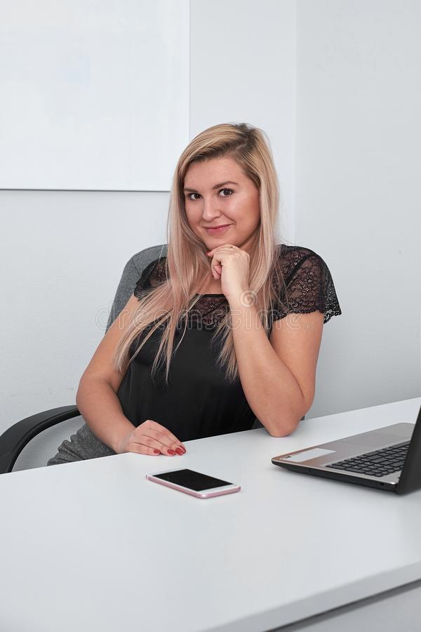 Cute young office worker in office stock photos