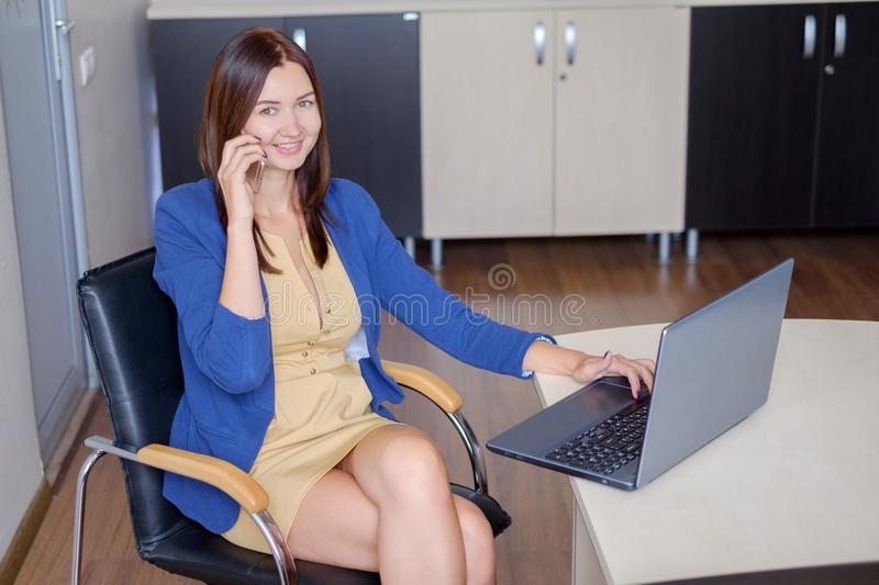 Cute young office worker talking on cell phone in office royalty free stock photos