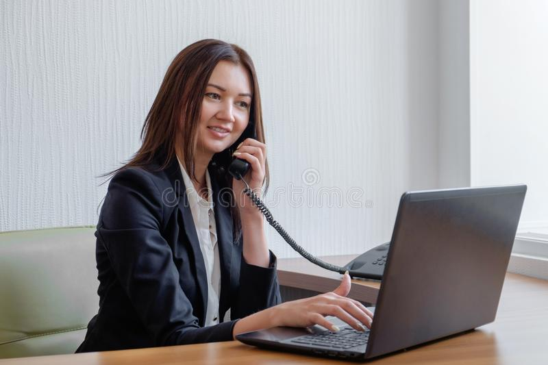 Cute young office worker talking on cell phone in office royalty free stock photography