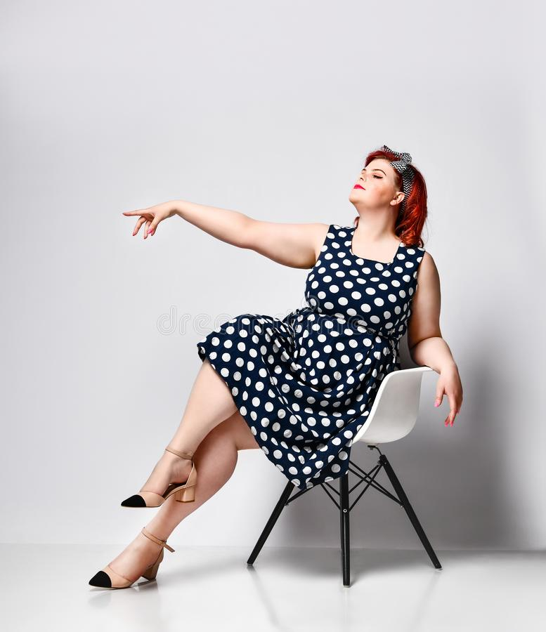 Pin up a female portrait. Beautiful retro fat woman in polka dot dress with red lips and old-style haircut stock images