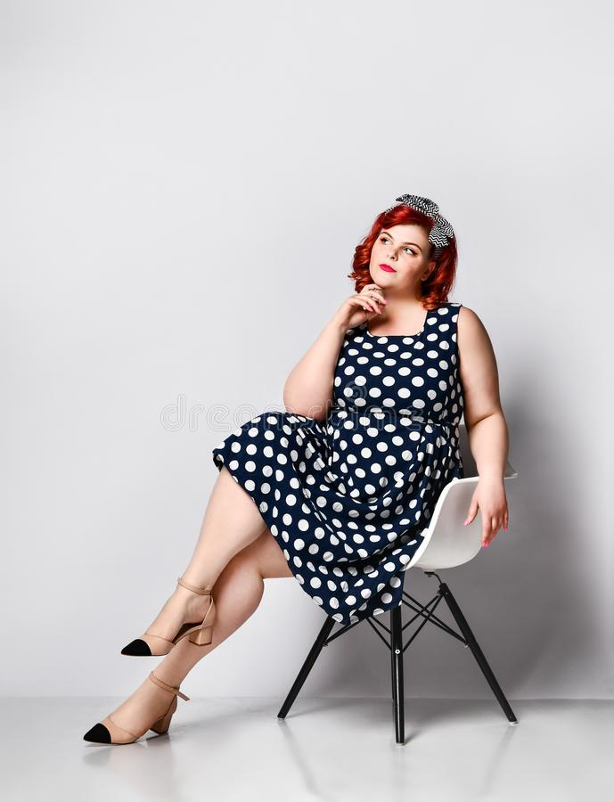 Pin up a female portrait. Beautiful retro fat woman in polka dot dress with red lips and old-style haircut. Cute young plus-sized girl wearing a polka-dot dress royalty free stock photos
