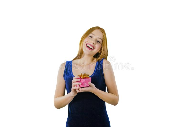 A cute young red-haired girl in a blue velvet evening dress with a box in her hands joyfully smiles with her head bowed stock photography