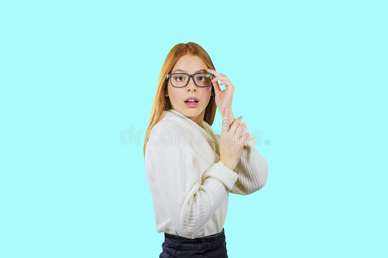 A cute young red-haired girl with glasses stands in profile with glasses on her hand, surprised, isolated background stock photos