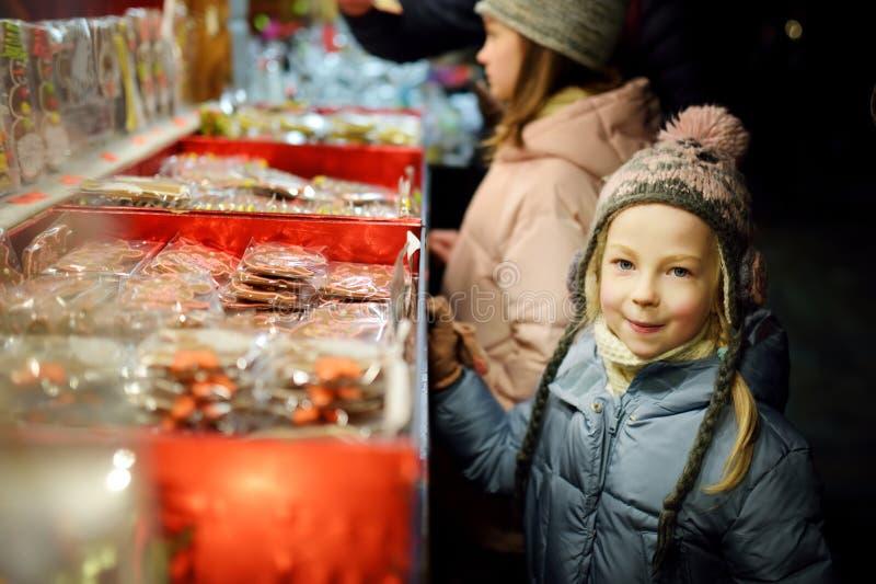 Cute young sisters som väljer sötsaker på den traditionella julmarknaden i Riga, Lettland Barn som köper godis och kakor på Xmas arkivfoto