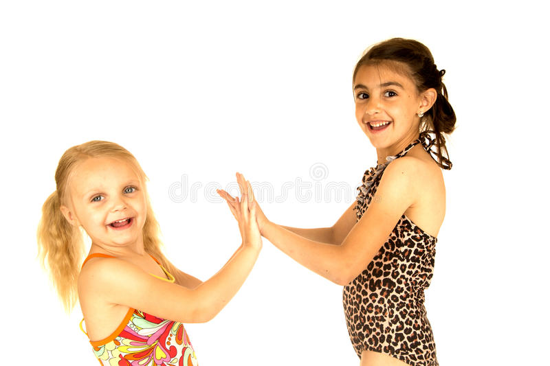 Cute young sisters wearing swimsuits playing patty cake smiling stock image
