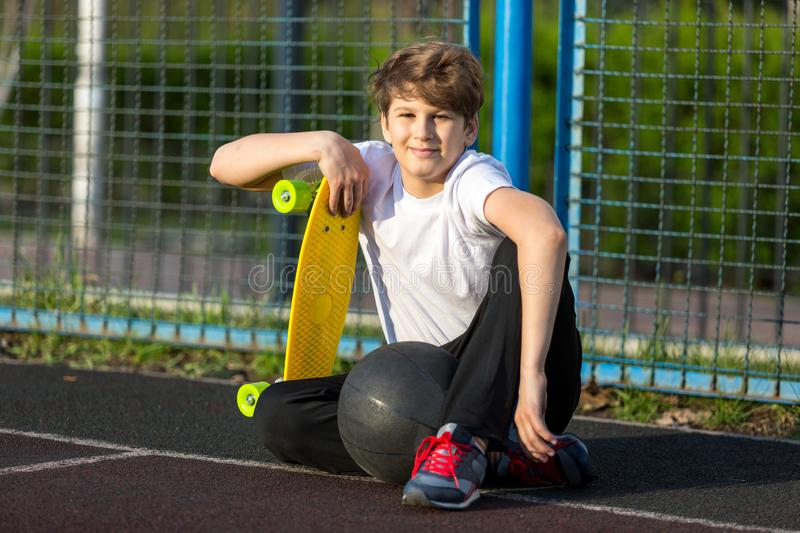 Cute young sport boy with yellow skateboard. He has a good time on his free time on weekend, holidayson sports ground. royalty free stock photos